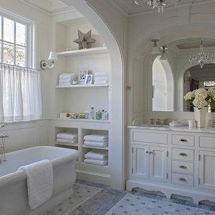 Foto di una stanza da bagno padronale stile marinaro con ante con riquadro incassato, ante bianche, vasca freestanding, vasca/doccia, pareti bianche, lavabo sottopiano, pavimento grigio e doccia aperta