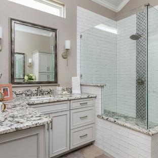 Mittelgroßes Shabby-Chic-Style Badezimmer En Suite mit profilierten Schrankfronten, beigen Schränken, Eckdusche, weißen Fliesen, Keramikfliesen, brauner Wandfarbe, Unterbauwaschbecken, Marmor-Waschbecken/Waschtisch, braunem Boden, Falttür-Duschabtrennung und bunter Waschtischplatte in Dallas
