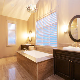 Example of a trendy beige tile alcove shower design in Calgary with a drop-in sink, raised-panel cabinets, dark wood cabinets and an undermount tub