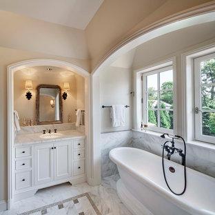 Diseño de cuarto de baño ecléctico, de tamaño medio, con puertas de armario blancas, bañera exenta, baldosas y/o azulejos multicolor, baldosas y/o azulejos de mármol, paredes beige, suelo de mármol, encimera de mármol y suelo multicolor