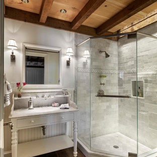 Example of a mid-sized eclectic white tile and marble tile medium tone wood floor and brown floor corner shower design in Other with white walls, a console sink and a hinged shower door