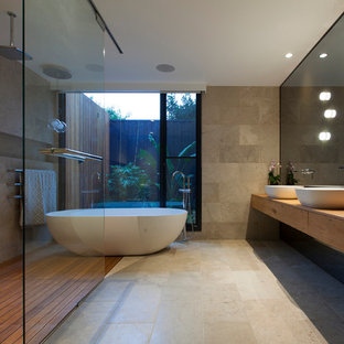 This is an example of a contemporary master bathroom in Melbourne with medium wood cabinets, a freestanding tub, an open shower, stone tile and a vessel sink.