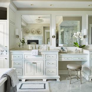 Стильный дизайн: огромная главная ванная комната в классическом стиле с белыми фасадами, отдельно стоящей ванной, угловым душем, серой плиткой, мраморной плиткой, бежевыми стенами, мраморным полом, врезной раковиной, столешницей из кварцита, белым полом, душем с распашными дверями, белой столешницей и фасадами с декоративным кантом - последний тренд
