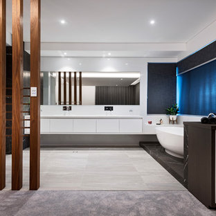 Inspiration for a modern bathroom in Perth with flat-panel cabinets, white cabinets, a freestanding tub, white walls, grey floor and white benchtops.