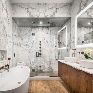 Modernes Badezimmer En Suite mit flächenbündigen Schrankfronten, freistehender Badewanne, Porzellanfliesen, Falttür-Duschabtrennung, weißer Waschtischplatte, Doppelwaschbecken, schwebendem Waschtisch, Duschnische, Fliesen in Holzoptik, Aufsatzwaschbecken und braunem Boden in New York