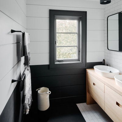 Bathroom - contemporary white tile and subway tile black floor bathroom idea in New York with flat-panel cabinets, light wood cabinets, multicolored walls, a vessel sink and wood countertops