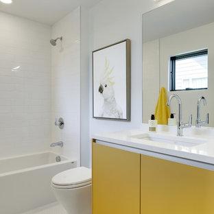 Immagine di una stanza da bagno con doccia contemporanea con ante lisce, ante gialle, vasca ad alcova, vasca/doccia, piastrelle bianche, pareti bianche, pavimento bianco e top bianco