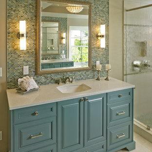 Bild på ett vintage badrum, med ett undermonterad handfat, luckor med upphöjd panel, blå skåp, blå kakel, mosaik, beige väggar och beiget golv