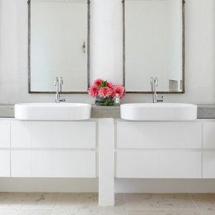 Diseño de cuarto de baño marinero con armarios con paneles lisos, encimera de cemento y paredes blancas