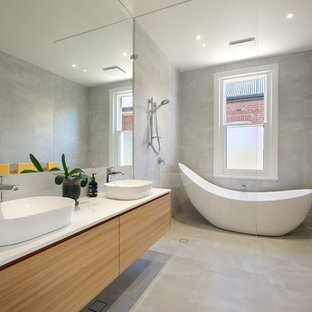 Photo of a mid-sized contemporary master wet room bathroom in Adelaide with light wood cabinets, a freestanding tub, gray tile, ceramic tile, ceramic floors, engineered quartz benchtops, grey floor, an open shower, white benchtops, flat-panel cabinets and a vessel sink.