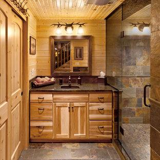 Diseño de cuarto de baño rural con lavabo bajoencimera, armarios con paneles lisos, ducha empotrada, suelo de pizarra, puertas de armario de madera oscura y baldosas y/o azulejos de pizarra
