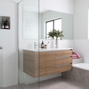 Immagine di una stanza da bagno scandinava con ante lisce, ante in legno scuro, vasca ad alcova, doccia ad angolo, pareti bianche, lavabo sottopiano, pavimento beige e top bianco