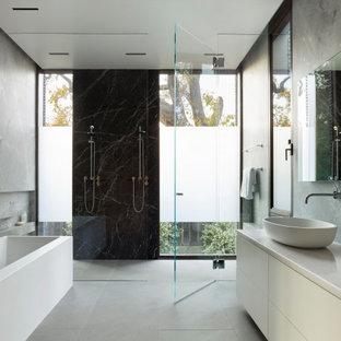 Ispirazione per una stanza da bagno minimalista con ante lisce, ante bianche, vasca freestanding, lavabo a bacinella, pavimento grigio e top bianco