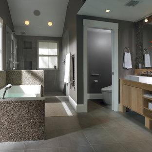 ボストンの大きいコンテンポラリースタイルのおしゃれなマスターバスルーム (ベッセル式洗面器、フラットパネル扉のキャビネット、アルコーブ型浴槽、アルコーブ型シャワー、グレーのタイル、淡色木目調キャビネット、セメントタイル、グレーの壁、木製洗面台、ベージュのカウンター) の写真