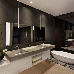 Photo of a large contemporary ensuite bathroom in Phoenix with flat-panel cabinets, white cabinets, a freestanding bath, black tiles, ceramic tiles, black walls, concrete flooring, an integrated sink, concrete worktops and grey floors.