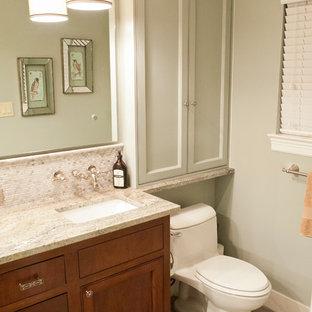Idee per una piccola stanza da bagno tradizionale con lavabo sottopiano, ante con riquadro incassato, ante in legno bruno, top in granito, WC monopezzo, piastrelle grigie, piastrelle in gres porcellanato, pareti verdi e pavimento in gres porcellanato