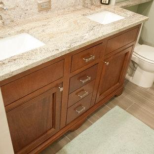 Modelo de cuarto de baño clásico renovado, pequeño, con lavabo bajoencimera, armarios con paneles empotrados, puertas de armario de madera en tonos medios, encimera de granito, sanitario de una pieza, baldosas y/o azulejos grises, baldosas y/o azulejos de porcelana, paredes verdes y suelo de baldosas de porcelana