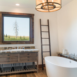 Freestanding bathtub - rustic master medium tone wood floor freestanding bathtub idea in Other with furniture-like cabinets, dark wood cabinets, white walls, a drop-in sink and multicolored countertops