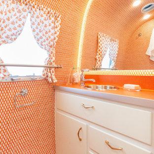 Inspiration för ett litet eklektiskt orange oranget badrum med dusch, med släta luckor, vita skåp, en toalettstol med hel cisternkåpa, orange kakel, orange väggar, målat trägolv, ett nedsänkt handfat, laminatbänkskiva och orange golv