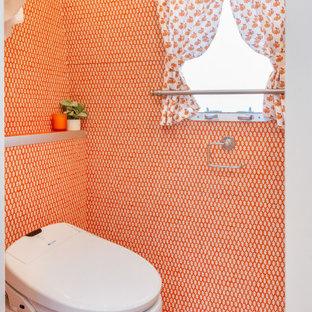 Modelo de cuarto de baño con ducha, ecléctico, pequeño, con armarios con paneles lisos, puertas de armario blancas, sanitario de una pieza, baldosas y/o azulejos naranja, parades naranjas, suelo de madera pintada, lavabo bajoencimera, encimera de laminado, suelo naranja y encimeras naranjas