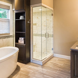 Bathroom - mid-sized transitional master beige tile and marble tile light wood floor, brown floor and double-sink bathroom idea in Dallas with raised-panel cabinets, dark wood cabinets, brown walls, an undermount sink, quartz countertops, a hinged shower door, gray countertops and a built-in vanity