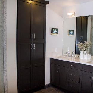 Bild på ett mellanstort vintage en-suite badrum, med luckor med profilerade fronter, skåp i mörkt trä, en hörndusch, grå kakel, porslinskakel, vita väggar, klinkergolv i porslin, ett undermonterad handfat, bänkskiva i akrylsten och en toalettstol med separat cisternkåpa