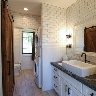 Foto de cuarto de baño principal, clásico renovado, de tamaño medio, con armarios con paneles empotrados, puertas de armario blancas, ducha abierta, sanitario de dos piezas, baldosas y/o azulejos blancos, baldosas y/o azulejos de cemento, paredes blancas, suelo de madera clara, lavabo sobreencimera y encimera de esteatita