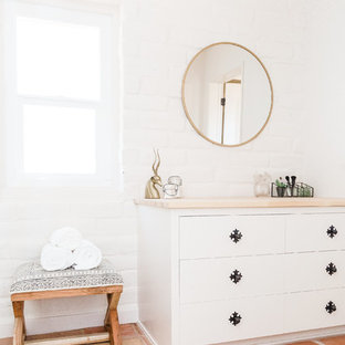 Inspiration for a southwestern terra-cotta tile and orange floor bathroom remodel in San Diego with furniture-like cabinets, white cabinets and white walls