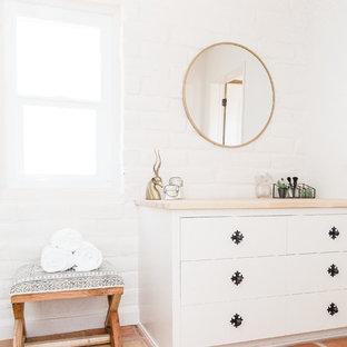 Inredning av ett amerikanskt badrum, med möbel-liknande, vita skåp, vita väggar, klinkergolv i terrakotta och orange golv