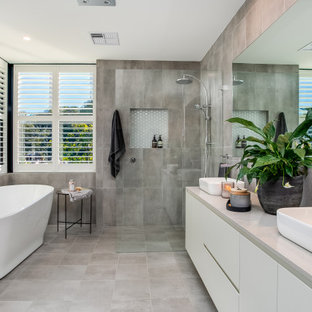 Design ideas for a contemporary bathroom in Sydney with flat-panel cabinets, white cabinets, a freestanding tub, gray tile, a vessel sink, grey floor and grey benchtops.