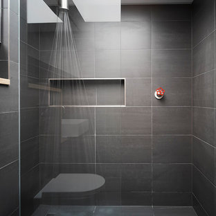 This is an example of an industrial bathroom in London with an alcove shower, gray tile and an open shower.