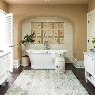 Modelo de cuarto de baño principal, clásico renovado, grande, con armarios con rebordes decorativos, puertas de armario blancas, bañera exenta, paredes marrones, suelo de madera oscura, lavabo bajoencimera, encimera de mármol y suelo marrón