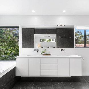 Design ideas for a mid-sized contemporary master bathroom in Brisbane with shaker cabinets, white cabinets, a hot tub, an alcove shower, a one-piece toilet, black and white tile, porcelain tile, black walls, porcelain floors, an undermount sink, engineered quartz benchtops, black floor, an open shower, white benchtops, a niche, a double vanity and a floating vanity.