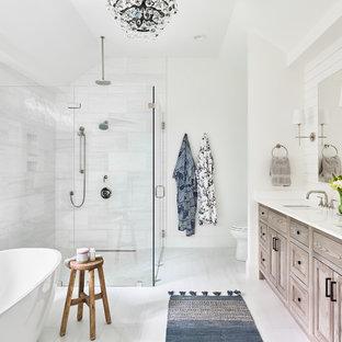 Maritim inredning av ett vit vitt en-suite badrum, med skåp i ljust trä, ett fristående badkar, en kantlös dusch, vit kakel, vita väggar, ett undermonterad handfat, vitt golv och dusch med gångjärnsdörr
