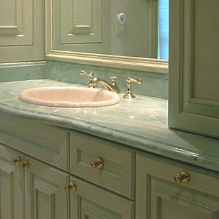 Large traditional family bathroom in Boston with recessed-panel cabinets, green cabinets, an alcove shower, a one-piece toilet, beige walls, limestone flooring, a submerged sink, marble worktops, beige floors and a hinged door.