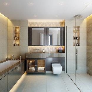 Foto di una stanza da bagno tradizionale con ante di vetro, ante marroni, vasca sottopiano, doccia a filo pavimento, WC sospeso, piastrelle beige, piastrelle marroni, lavabo sottopiano, porta doccia a battente e top grigio