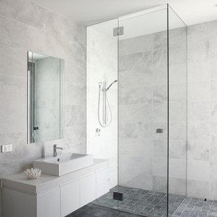 Ejemplo de cuarto de baño actual con armarios con paneles lisos, puertas de armario blancas, ducha a ras de suelo, baldosas y/o azulejos grises, paredes grises y suelo gris