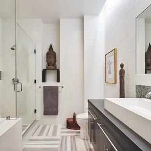 Modelo de cuarto de baño principal, de estilo zen, con armarios con paneles lisos, puertas de armario grises, ducha esquinera, baldosas y/o azulejos blancos, paredes blancas, lavabo sobreencimera, suelo multicolor, ducha con puerta con bisagras y encimeras grises