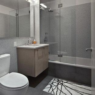 Idée de décoration pour une salle de bain design avec une baignoire en alcôve, un carrelage gris, un placard à porte plane, des portes de placard en bois clair, un WC séparé, des carreaux de porcelaine, un mur gris, un sol en carrelage de porcelaine, un lavabo encastré et un plan de toilette en quartz modifié.