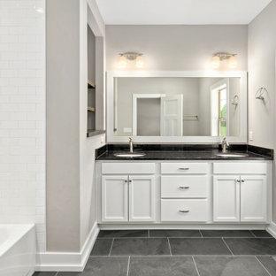 Modelo de cuarto de baño principal, de estilo americano, de tamaño medio, con armarios con paneles lisos, puertas de armario blancas, ducha empotrada, sanitario de una pieza, paredes grises, suelo de baldosas de cerámica, lavabo bajoencimera, encimera de granito, suelo negro, ducha con cortina y encimeras negras