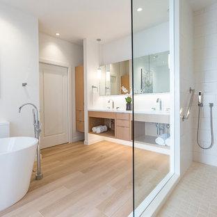 Inspiration för mellanstora moderna en-suite badrum, med släta luckor, skåp i ljust trä, ett fristående badkar, en öppen dusch, en toalettstol med hel cisternkåpa, vit kakel, porslinskakel, vita väggar, klinkergolv i porslin, ett integrerad handfat och bänkskiva i akrylsten