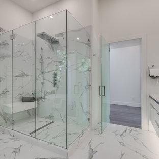Пример оригинального дизайна интерьера: главная ванная комната в стиле модернизм с стеклянными фасадами, белыми фасадами, отдельно стоящей ванной, открытым душем, белой плиткой, каменной плиткой, белыми стенами, мраморным полом, настольной раковиной, столешницей из искусственного кварца, белым полом, душем с распашными дверями, белой столешницей и инсталляцией