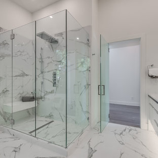 Modern master bathroom in Vancouver with glass-front cabinets, white cabinets, a freestanding tub, an open shower, white tile, stone tile, white walls, marble floors, a vessel sink, engineered quartz benchtops, white floor, a hinged shower door, white benchtops and a wall-mount toilet.