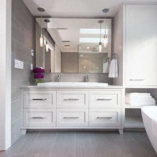 Foto de cuarto de baño principal, actual, de tamaño medio, con lavabo de seno grande, armarios estilo shaker, puertas de armario grises, encimera de cuarcita, bañera exenta, ducha esquinera, sanitario de una pieza, baldosas y/o azulejos grises, baldosas y/o azulejos de porcelana, paredes grises y suelo de baldosas de porcelana
