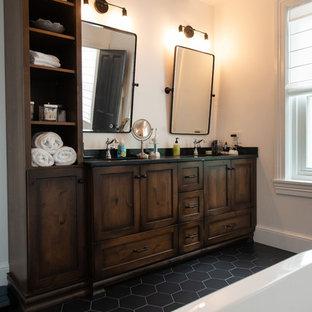 Modelo de cuarto de baño ecléctico con bañera exenta, paredes blancas, encimera de esteatita y encimeras negras