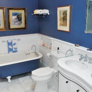 Imagen de cuarto de baño principal, costero, con armarios tipo mueble, puertas de armario blancas, bañera con patas, paredes azules, suelo de mármol, lavabo integrado, encimera de esteatita, suelo blanco y encimeras blancas