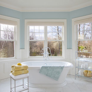 Large elegant master white tile porcelain floor freestanding bathtub photo in Portland with recessed-panel cabinets, blue walls and marble countertops