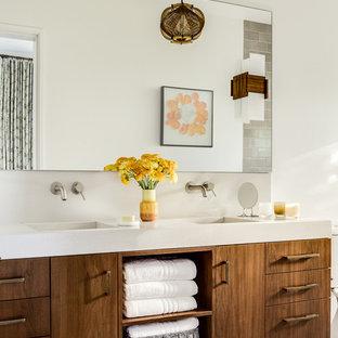 Foto de cuarto de baño asiático con armarios con paneles lisos, puertas de armario marrones, paredes blancas, suelo de cemento, lavabo integrado y suelo gris