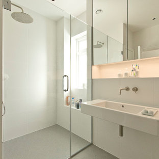 This is an example of a modern bathroom in London with a built-in shower, white tiles, a wall-mounted sink, grey floors and a hinged door.