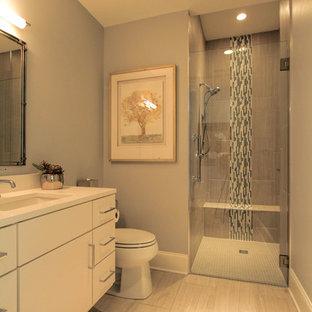 Ispirazione per una stanza da bagno padronale moderna di medie dimensioni con ante lisce, ante bianche, doccia a filo pavimento, WC a due pezzi, piastrelle di vetro, pareti grigie, pavimento con piastrelle in ceramica, lavabo sottopiano e top in superficie solida